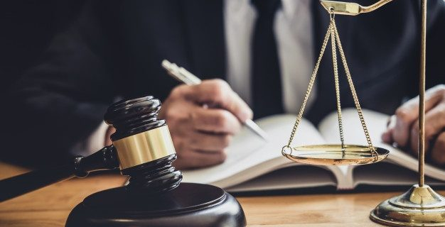 professional-male-lawyer-judge-working-with-contract-papers-documents-gavel-scales-justice-table-courtroom-law-legal-services-concept_28283-1373